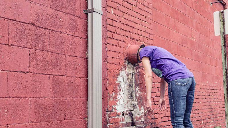 Lady with bucket on head hitting a brick wall